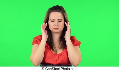 Portrait of cute girl suffering from headache from fatigue. Chubby girl in a coral dress with straight hair medium length and light eyes on green screen at studio