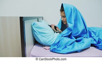 Portrait of cute girl under blanket with smartphone. little...