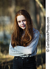 Portrait of cute girl with fiery red hair in the park.