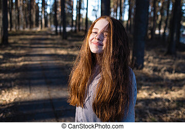 Portrait of cute girl with long bright red hair in the pine park.