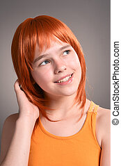 Portrait of cute girl with red hair posing in studio