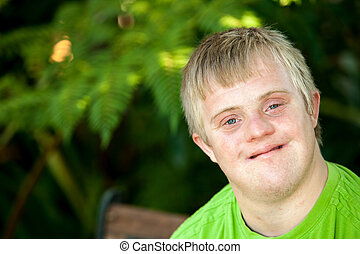 Portrait of cute handicapped boy in garden. - Close up face ...