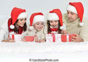 Portrait of cute happy family in Santa hats with gifts