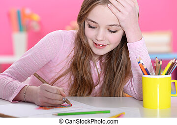 Portrait of cute happy girl drawing at home