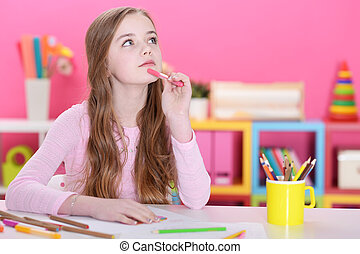 Portrait of cute happy girl drawing with pencils at home