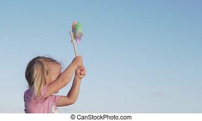 Portrait of cute happy girl having fun with pinwheel