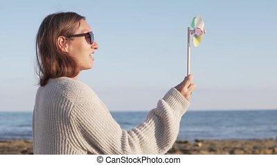 Portrait of cute happy girl having fun with pinwheel on the beach