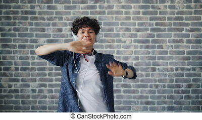 Portrait of cute hipster dancing in headphones on brick background having fun