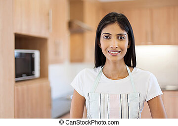 indian woman in kitchen with apron