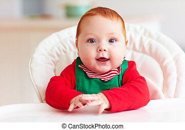 portrait of cute infant baby boy in elf costume sitting in...