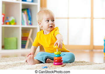 Portrait of cute kid boy assembling colorful pyramid toy on floor at living room