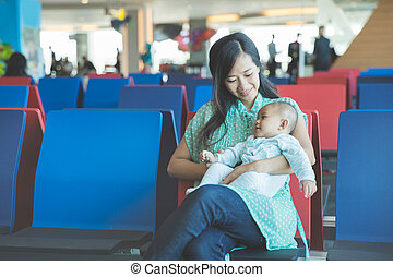 cute little baby waiting in the airport with her mother
