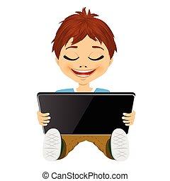 little boy having fun playing using digital tablet
