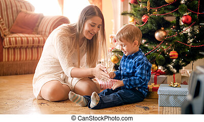 Portrait of cute little boy having fun with mother on Christmas morning at living room