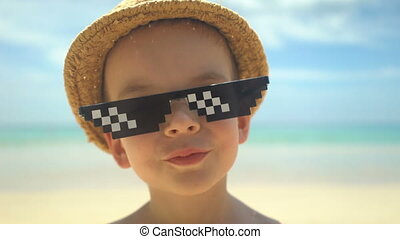 portrait of cute little boy in straw hat with sunglasses standing on summer beach.