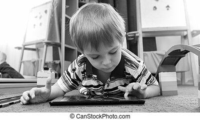 Portrait of cute little boy playing games on tablet lying on carpet at living room