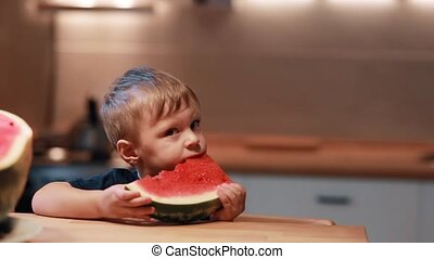 Portrait of cute little boy sitting at the table on the kitchen. Holding a piece and eating a watermelon.