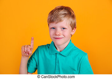 Portrait of cute little boy with finger pointed up