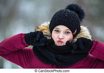 Portrait of cute little girl grimaces the face of outdoor at winter.