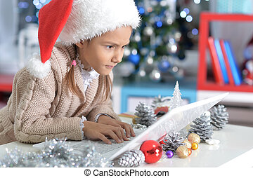 little girl in Santa hat with laptop