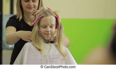 Portrait of cute little girl in hairdressing salon -...