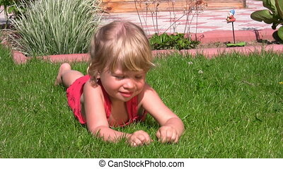 little girl lying in outlet and picks grass - portrait of...