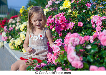 Portrait of cute little girl near the flowers in the yard of...