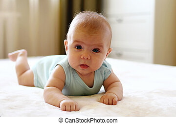 Portrait of cute little girl on a bed.