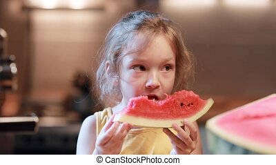 Portrait of cute little girl on the kitchen holding a chunk...