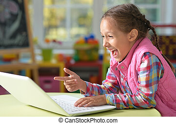 girl sitting at the table with laptop