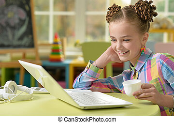 Portrait of cute little girl sitting at the table