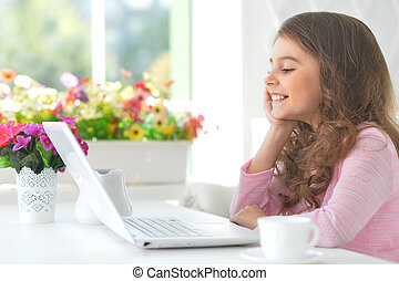 little girl sitting at the table with laptop