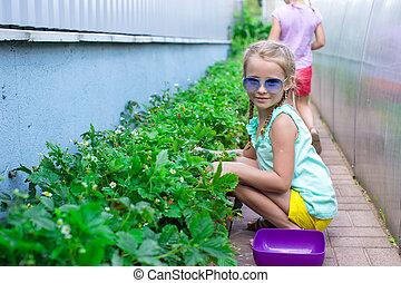 Portrait of cute little girl sitting in the garden