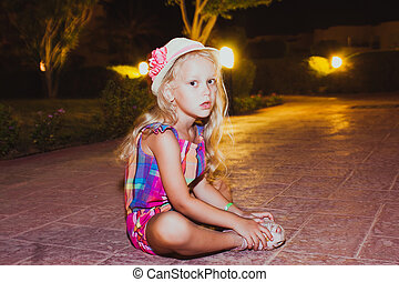 Portrait of cute little girl sitting on the ground.