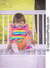 cute little girl sitting on wooden bench