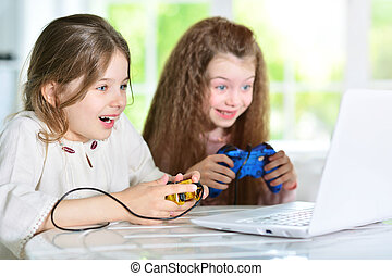 Portrait of cute little girls playing video game