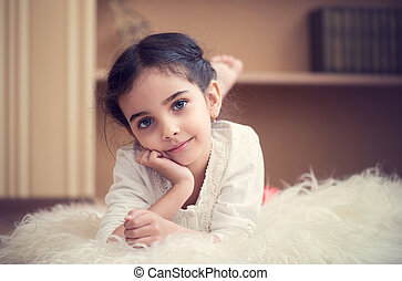 Portrait of cute little latino girl lying on wite carpet