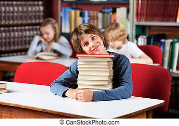 Portrait of cute little schoolboy sitting with stack of books at table in library and classmates in background
