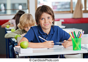 Portrait of cute little schoolboy smiling while sitting with classmates in a row at desk