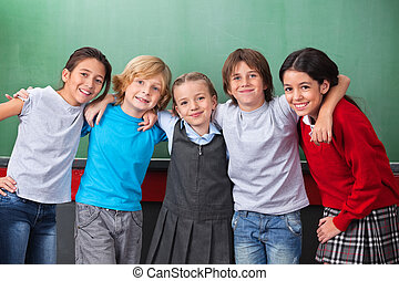 Portrait of cute little schoolchildren with arms around standing together against chalkboard in classroom