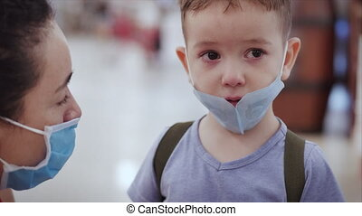 Portrait of cute mom and little boy child in a mask from viruses epidemic coronavirus upset wipes tears from eyes with hands looking at camera people are afraid upset child looks around.