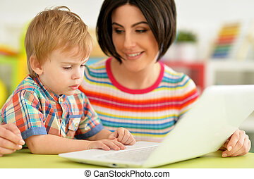 Portrait of cute mother and son using laptop together