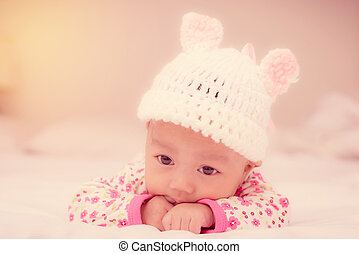 Portrait of cute newborn baby girl on the bed