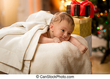 cute newborn baby lying on stomach next to Christmas gifts