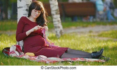 Portrait of cute pregnant woman with belly in autumn park make hobby knitting needles