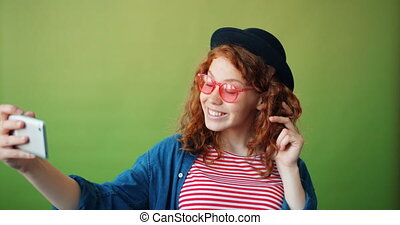 Portrait of cute redhead girl taking selfie with smartphone...