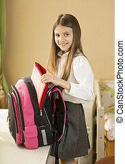 Portrait of cute schoolgirl packing her bag at bedroom