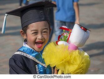 Portrait of cute schoolgirl with graduation hat.