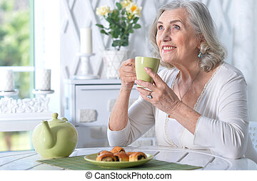 Portrait of cute senior woman having breakfast