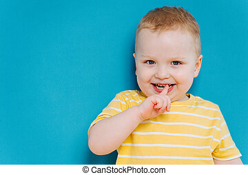 Portrait of cute shy blond little toddler boy in T-shirt